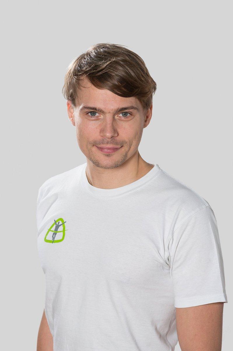 Das Foto zeigt Matthias Rocktäschel aus Dresden. Er hat kurze braune Haare und hat einen leichten Bart. Auf dem Foto steht er vor einem weißen Hintergrund und trägt ein weißes T-Shirt mit einem Praxislogo Aufdruck.