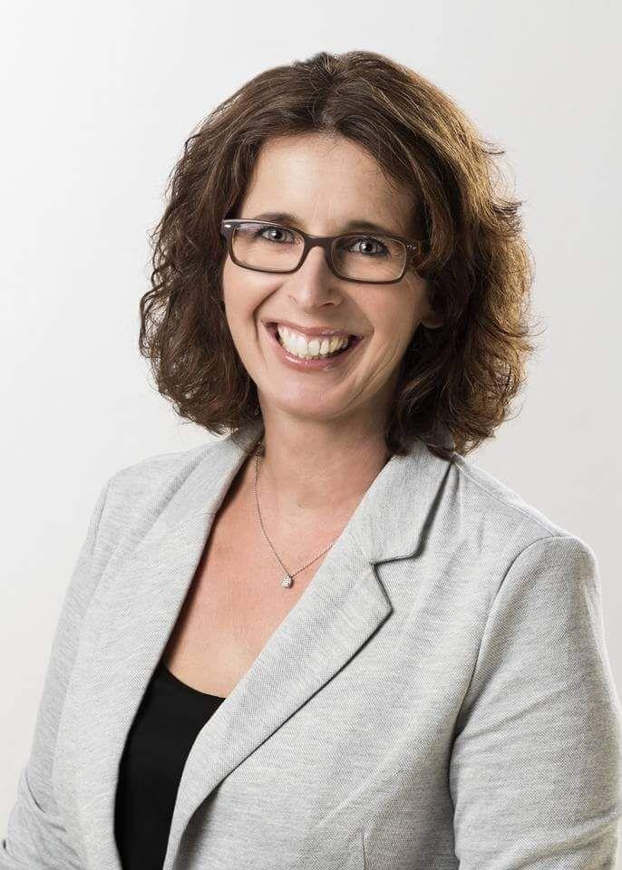 Das Portraitfoto zeigt Stefanie Tröbs - Kütemann vor einem weißen Hintergrund. Sie hat braune schulterlange Haare, die sich leicht locken und eine eckige braune Brille. Sie lacht und schaut in die Kamera. Auf dem Foto trägt sie einen grauen Blazer, eine s