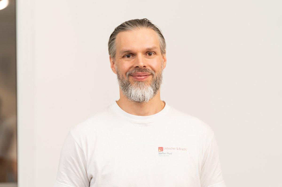 Das Foto zeigt den Rostocker Steffen Plust vor weißem Hintergrund. Er hat ein Liebscher & Bracht T-Shirt an und hat dunkelgraue Haare sowie einen hellgrauen Vollbart.