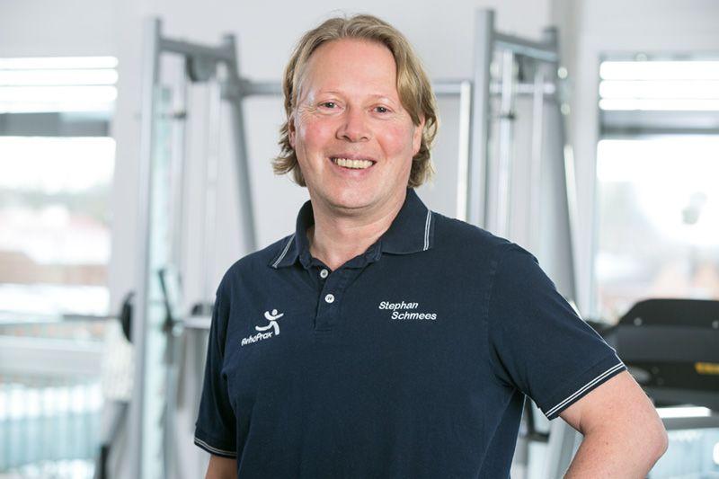 Das Foto zeigt Stephan Schmees aus 48431 Rheine. Im Hintergrund sind Trainingsgeräte und 2 Fenster zu sehen. Er hat mittellange blonde Haare und trägt ein blaues Polo T-Shirt mit weißer Aufschrift.
