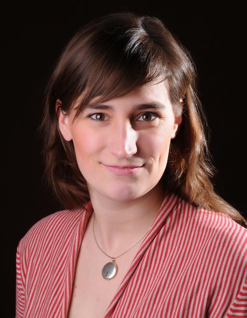 Auf dem Foto wurde Dr. Susanne Balzer vor einem schwarzen Hintergrund aufgenommen. Sie hat lange braune Haare mit einem seitlichen Scheitel. Dazu trägt sie eine rot-weiß gestreifte Blus und eine Kette mit einem silbernen Anhänger.