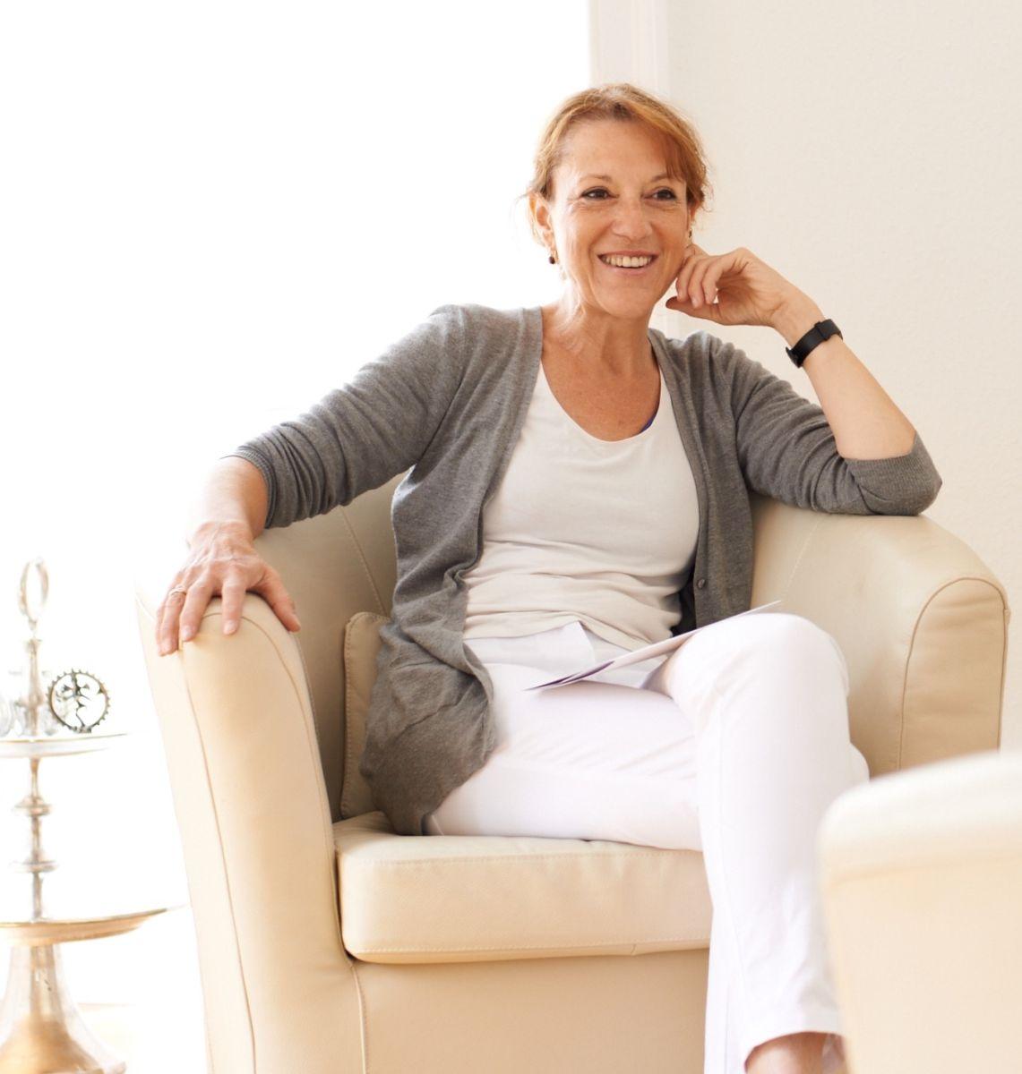Susanne Wenzel aus Wiesbaden sitzt auf einem hellen Sessel und hat ihre Beine übereinander geschlagen. Sie stützt Ihren Kopf mit einer Hand ab, die auf der Sessellehne liegt. Sie lacht herzlich und schaut geradeaus. Ihr langen rot braunen Haare trägt sie