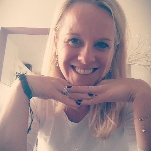 Das Foto zeigt Tamara Malinka-Eul aus Rheinbach. Sie hat ihren Kopf auf ihre Hände abgestützt und schaut lächelnd in die Kamera. Sie hat lange blonde Haare und trägt eine weiße Bluse und silbernen Schmuck sowie ein schwarzes Armband.