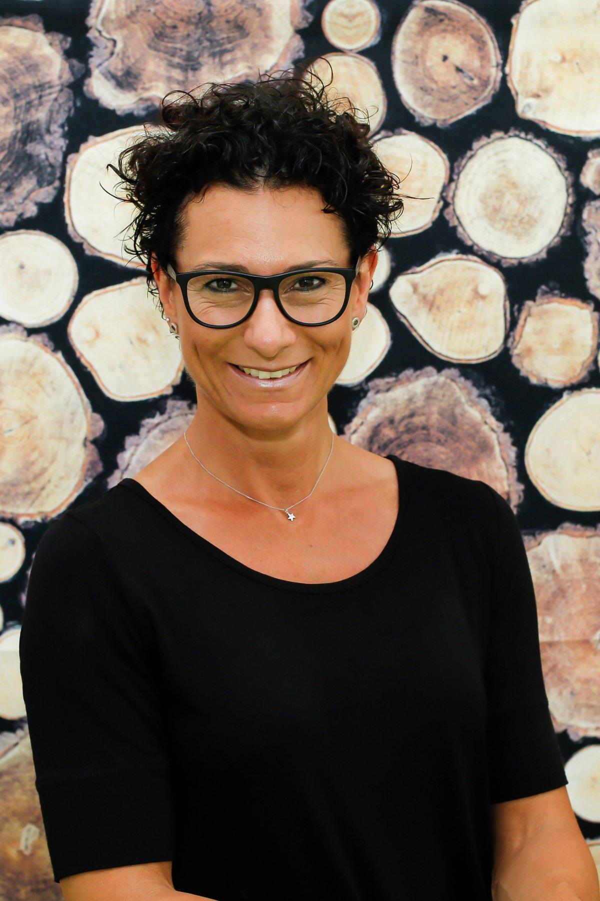 Auf dem Foto sieht man Tanja Missner aus Schwerte vor gestapelten Holzbäumen. Sie hat kurze schwarze Haare, die sich locken. Sie trägt eine schwarze eckige Brille, ein schwarzes T-Shirt sowie eine silberne Kette.
