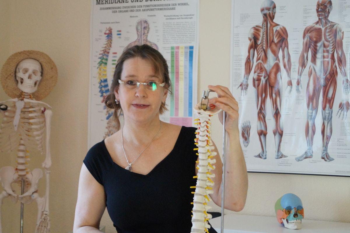 Auf dem Bild ist Tanja Wiemann-Kranz aus Bochum zu sehen. Sie hält eine Skelett Wirbelsäule in der Hand und im Hintergrund sind ebenfalls anatomische Plakate und ein Modellskelett zu sehen. Sie hat kinnlange braune Haare und trägt eine rahmenlose Brille.