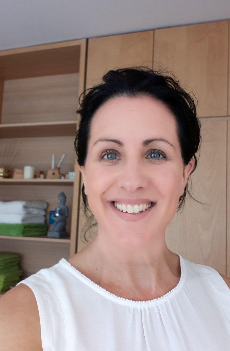 Auf dem Foto ist Tanja Zimmermann aus Coburg zu sehen. Sie trägt ihre schwarzen Haare als Zopf und eine weiße kurzärmlige Bluse. Im Hintergrund sieht man eine Regalwand.