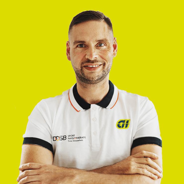 Das Foto zeigt Timo Grauerholz vor einem gelben Hintergrund. Er schaut gerade in die Kamera und hat die Arme vor der Brust verschränkt. Er hat kurze braune Haare, einen Dreitagebart und trägt ein Polo T-Shirt mit schwarzen Rand.