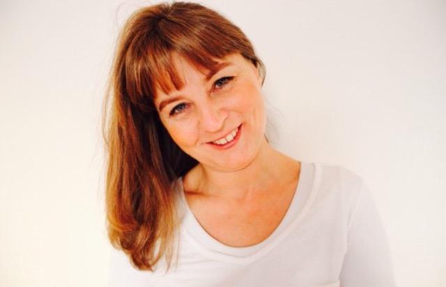 Die junge Ursula Alma Fecher aus Eibelstadt steht sympathisch vor einem weißen Hintergrund. Sie hat rot braune lange Haare mit Pony und trägt ein weißes T-Shirt.