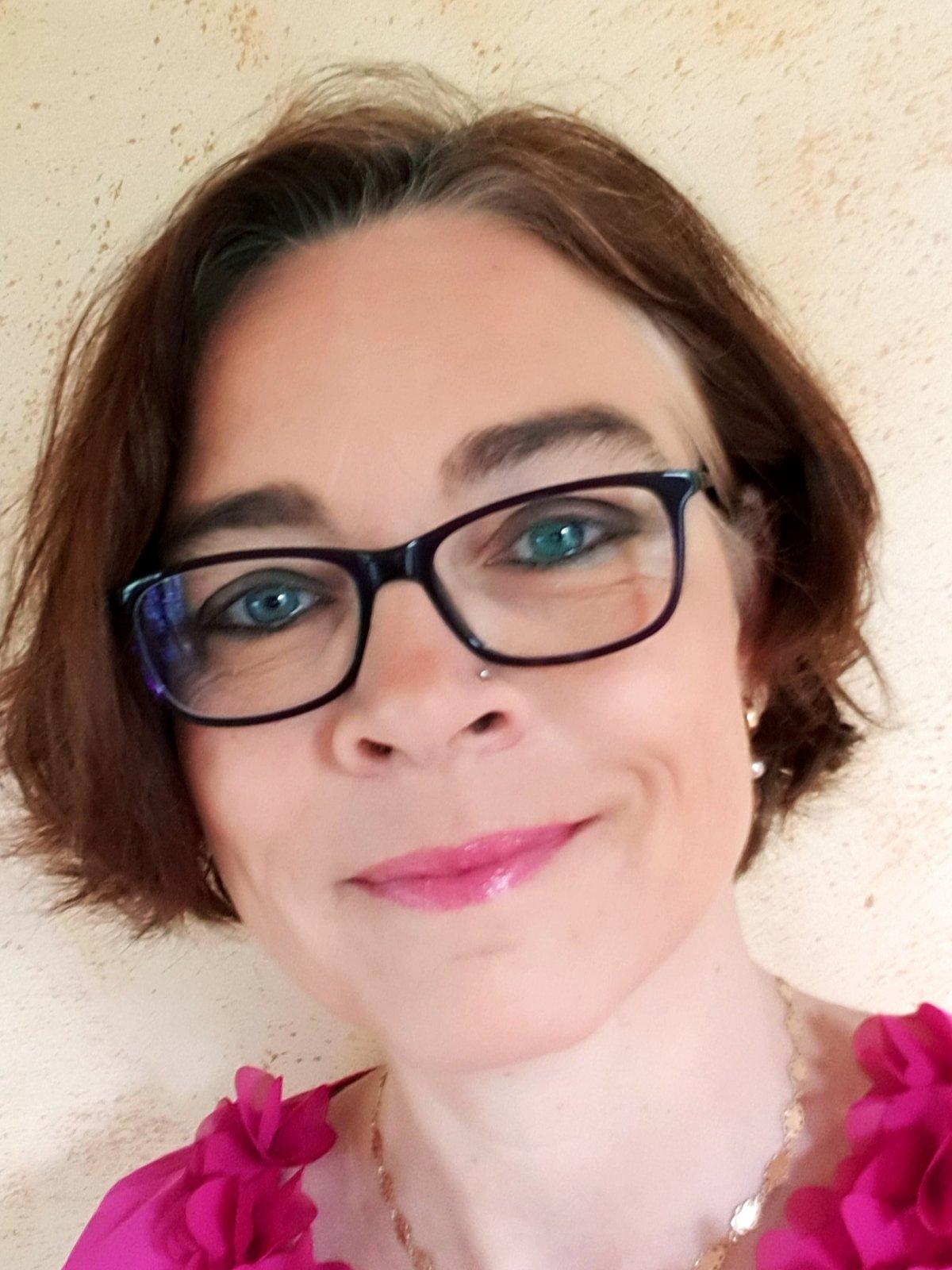 Das Foto zeigt Ursula Wirz aus Basel vor einem hellgelben Hintergrund. Sie hat kinnlange braune Haare und einen Nasenpiercing. Sie trägt eine eckige dunkle Brille und eine rosa Bluse.