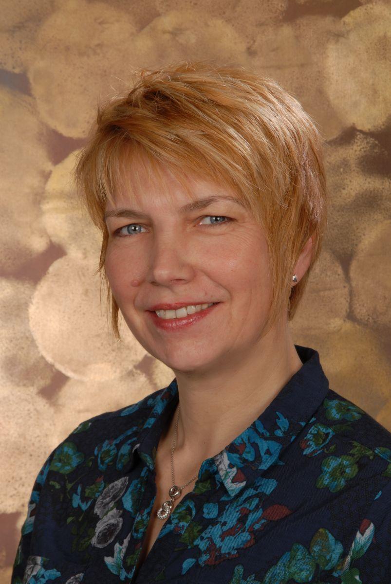 Das Foto zeigt die Physiotherapeutin Uschi Hermes vor einem Hintergrund mit großen hellbraunen Kreisen. Sie hat kurzes rot-blondes Haar und trägt auf dem Foto eine blau gemusterte Bluse und eine silberne Kette.