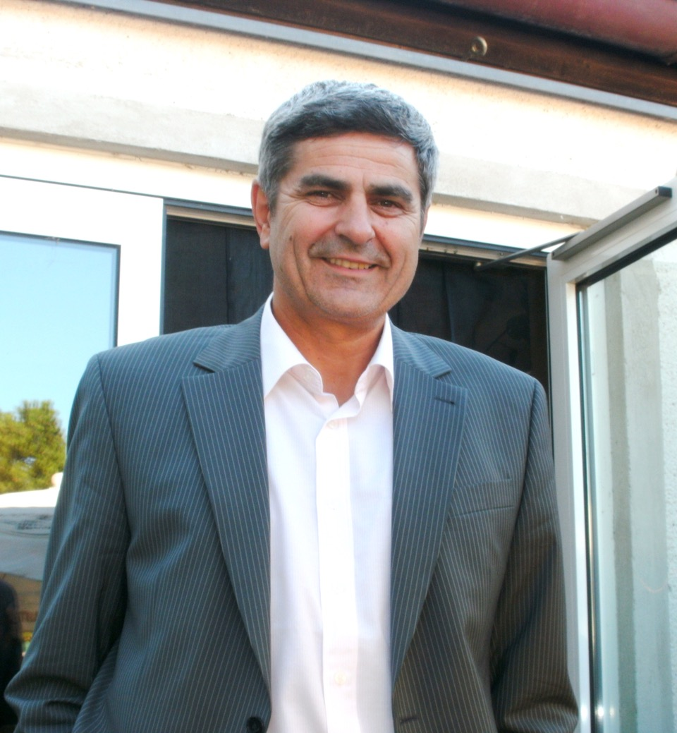 Das Foto zeigt Viorel Pop aus Straubing. Er hat dunkelgraue Haare und lächelt in die Kamera. Auf dem Foto trägt er einen grau gestreiften Blazer und ein weißes Hemd.
