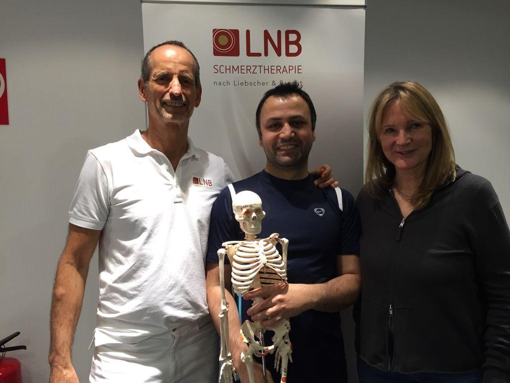 Das Foto zeigt Wasi Behzad aus Leipzig neben Roland Liebscher-Bracht und Dr. Petra Bracht. Er hält in der Hand ein Modellskelett und lächelt in die Kamera. Behzad hat kurze braune Haare und ein dunkelblaues T-Shirt an.