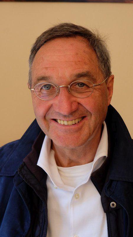 Auf dem Foto steht Werner Zaugg aus Arnstein / Binsfeld vor einem gelben Hintergrund. Er hat dunkelgraue Haare und trägt eine silberne runde Brille sowie ein weißes Hemd und eine blaue Jacke. Er lacht in die Kamera.