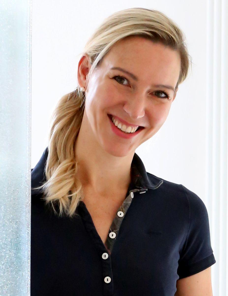 Das Foto zeigt Yvonne Schöpke aus München. Sie hat lange blonde Haare, die sie als Zopf trägt und über Ihre Schulter fällt. Sie trägt ein dunkelblaues Polo T-Shirt und lacht in die Kamera.