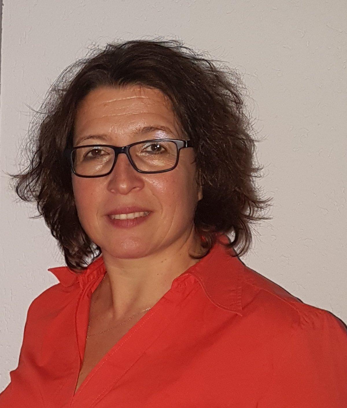 Auf dem Foto sieht man Zoe Bonidis aus Keltern Dietlingen vor einem hellen Hintergrund. Sie hat braune kinnlange Haare und trägt eine eckige dunkle Brille. Dazu hat sie auf dem Foto eine rote Bluse an.