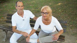 Ein Mann - Roland Liebscher - sitzt auf einer Parkbank links neben einer Frau, die als Übung gegen Hüftschmerzen ihr linkes Bein über ihr Rechtes im rechtwinkligem Winkel gelegt hat und mit geradem Rücken sich nach vorne zieht