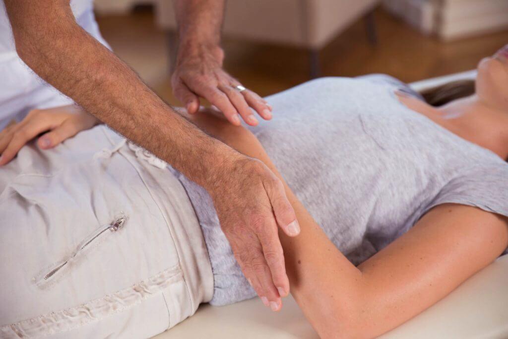 Roland Liebscher-Bracht zeigt einer Frau eine Übung im Armbereich.