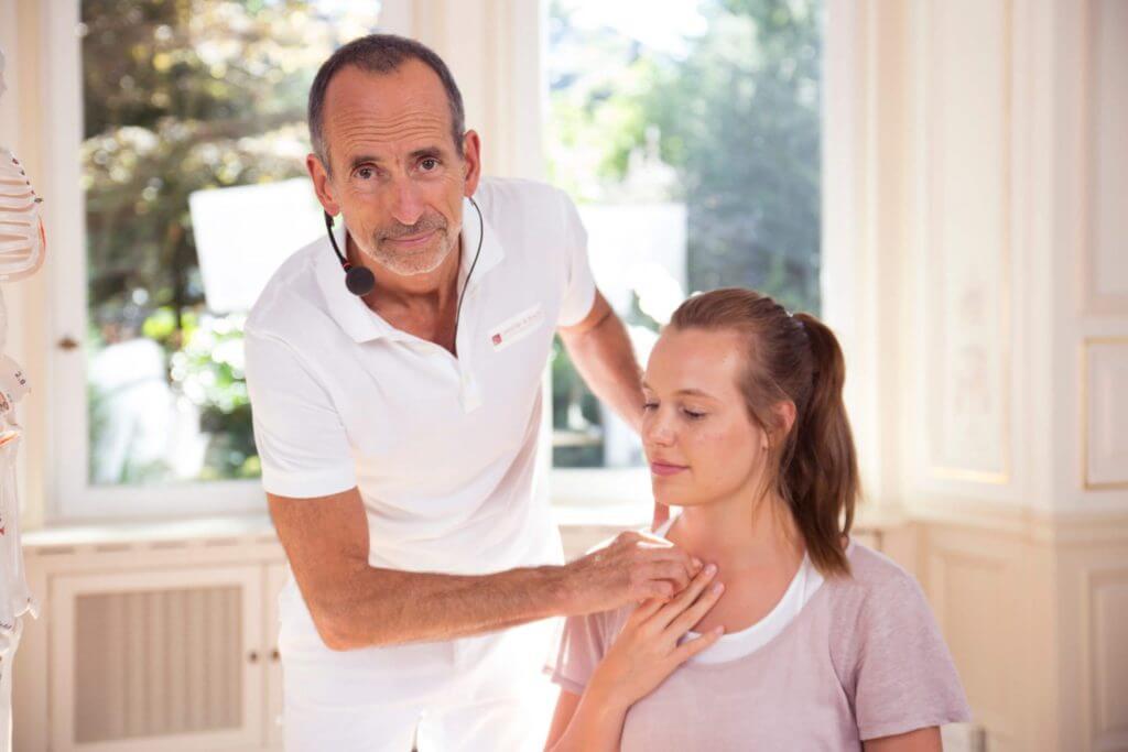Roland Liebscher-Bracht zeigt einer Frau eine Übung am Brustkorb.