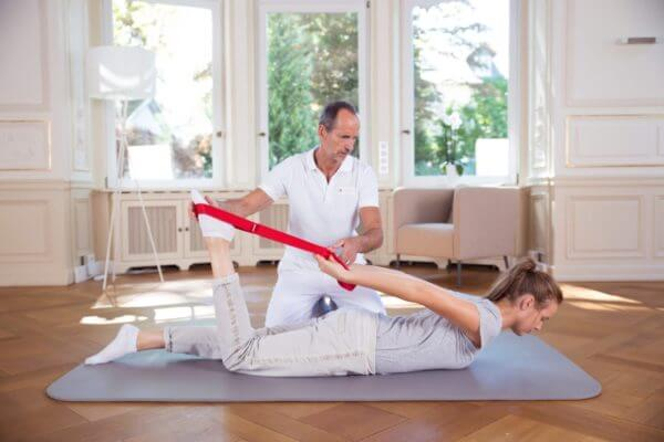Roland Liebscher-Bracht zeigt einer Frau, die auf dem Bauch auf dem Boden liegt, eine Übung und benutzt als Hilfmittel die Übunsschlaufe.