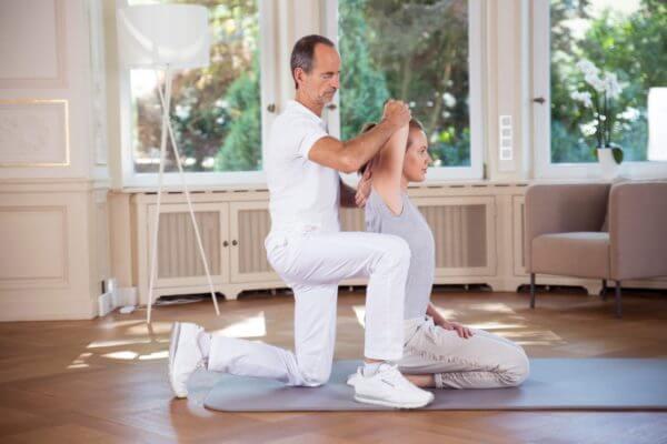 Eine Frau sitzt auf einer Übungsmatte. Hinter ihr kniet Roland Liebscher-Bracht und dehnt ihren Arm über ihren Kopf nach hinten.