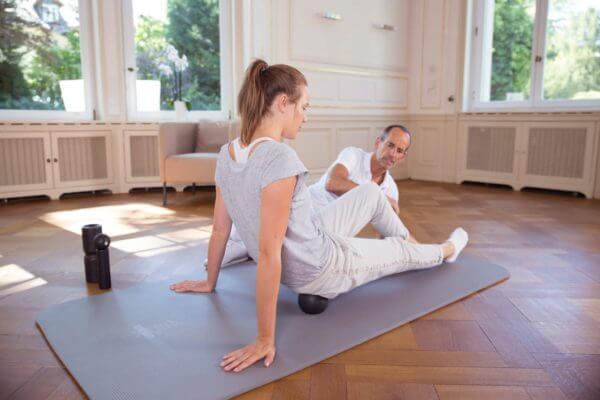 Roland Liebscher-Bracht zeigt einer Frau Übungen mit der Medifaszienkugel.