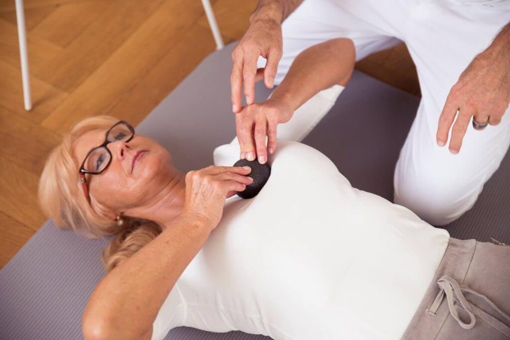 Roland Liebscher-Bracht zeigt einer Frau eine Übung mit der Mini-Faszienkugel eine Übung im Brustbereich.