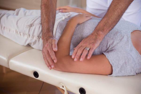Roland Liebscher-Bracht zeigt einer Frau eine Übung an ihrem Arm..
