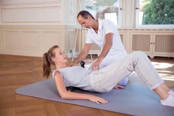 Roland Liebscher-Bracht zeigt einer Frau Rückenübungen mit Faszienrollen. Sie liegt dabei auf rücklings auf einer Bodenmatte.