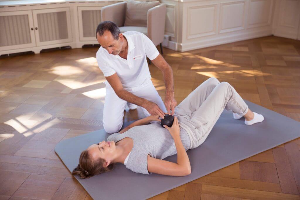 Roland Liebscher-Bracht zeigt einer Frau eine Übung am Boden mit der Medi-Faszienkugel im Bauchbereich.