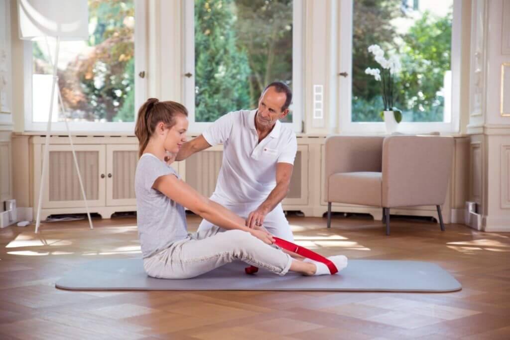 Roland Liebscher-Bracht zeigt einer Frau eine Übung mit der Übungsschlaufe. Die Schlaufe liegt um ihren Füßen, Beine leicht angewinkelt, sie sitzt aufrecht und zieht daran.