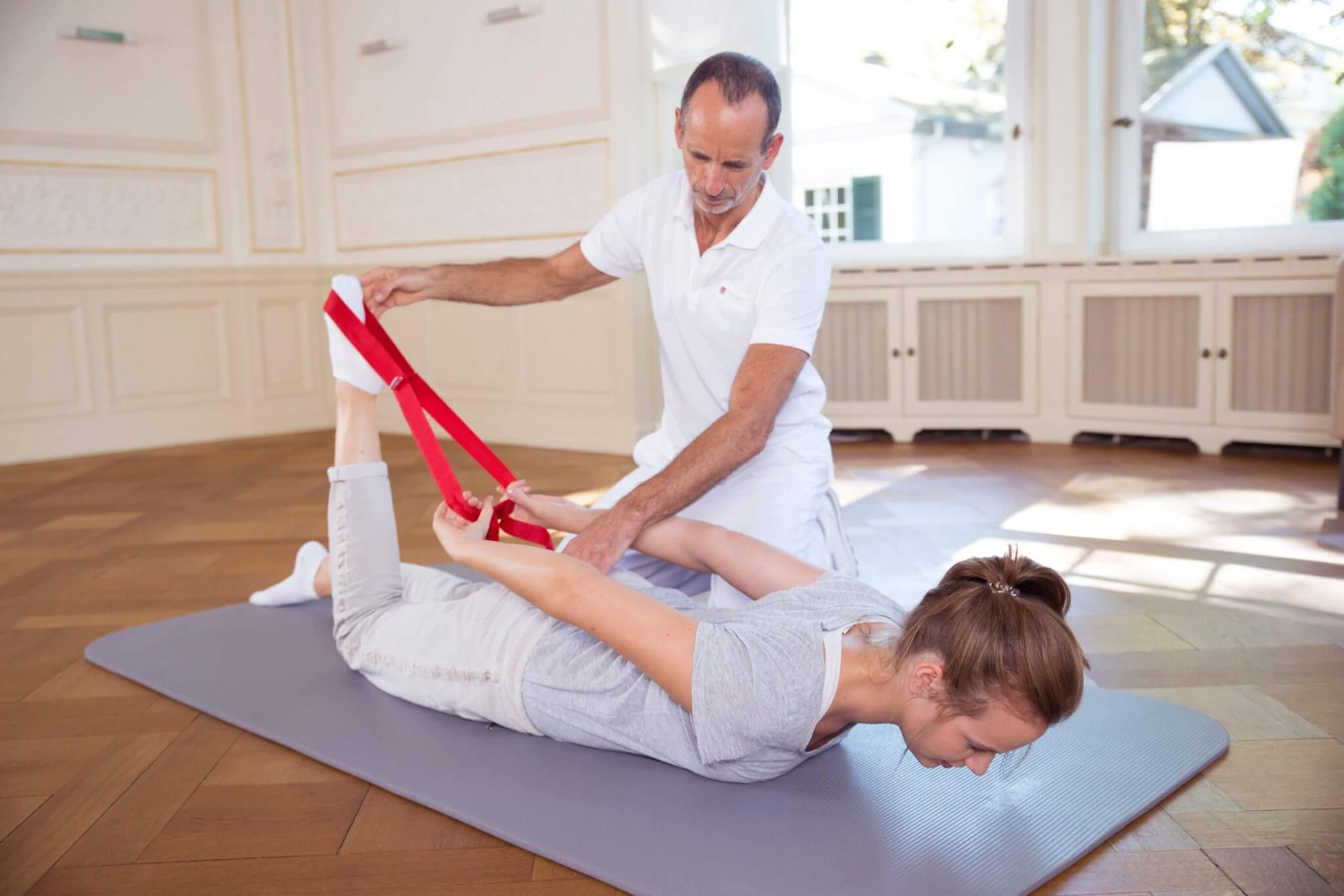 Roland Liebscher-Bracht zeigt einer Frau eine Übung. Sie liegt dabei bäuchlings auf dem Boden und zieht ihr Bein mithilfe der Übungsschlaufe in Richtung Gesäß.