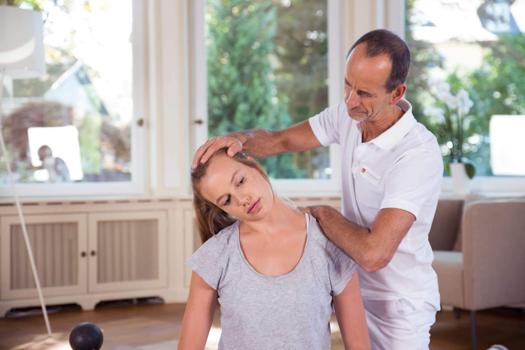 Roland Liebscher-Bracht zeigt einer Frau eine Dehnübung im Nackenbereich.