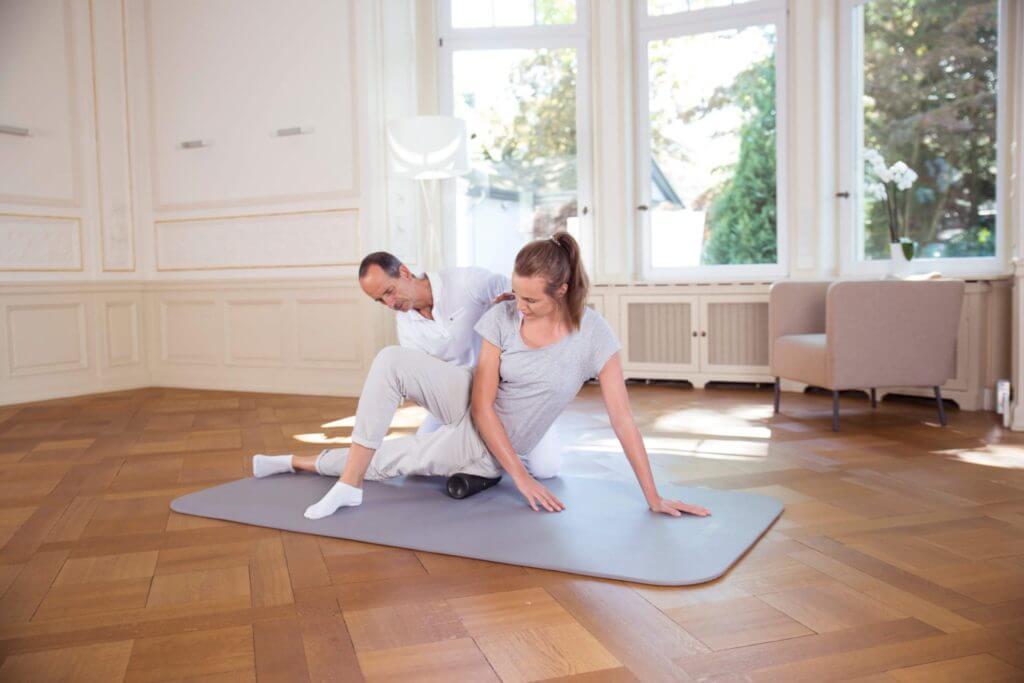 Roland Liebscher-Bracht zeigt einer Frau eine Übung mit einer Faszienrolle.
