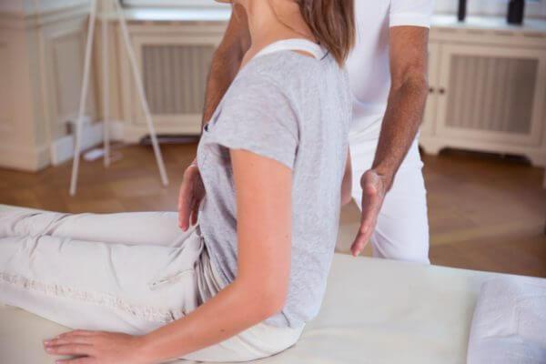 Roland Liebscher-Bracht zeigt einer Frau eine Übung und deutet dabei auf ihren Oberkörper. Sie sitzt auf einer Liege.