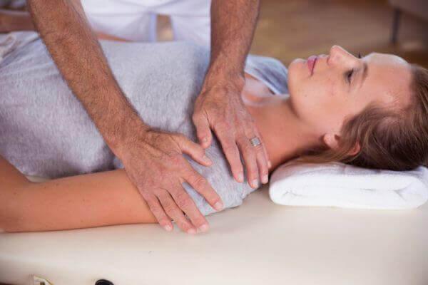Roland Liebscher-Bracht zeigt einer Frau eine Übung und drückt dabei sanft auf ihre Schulter. Sie liegt auf dem Rücken.