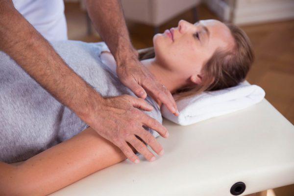 Roland Liebscher-Bracht zeigt einer Frau eine Übung. Sie liegt auf dem Rücken, er deutet auf ihre Schulter.