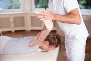 Roland Liebscher-Bracht zeigt einer Frau Übungen. Sie liegt bäuchlings, er unterstützt die Dehnung in Arm und Hand.