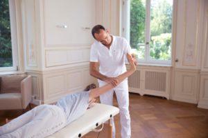 Roland Liebscher-Bracht zeigt Übungen gegen das KarpaltunnelsyndromRoland Liebscher-Bracht zeigt einer Frau Übungen. Sie liegt bäuchlings, er unterstützt die Dehnung in Arm und Hand.