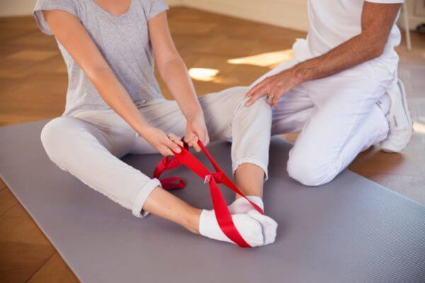 Roland Liebscher-Bracht zeigt einer Frau eine Übung. Sie sitzt und hat die Übungsschlaufe um beide Füße gelegt, sie zieht an der Schlaufe.