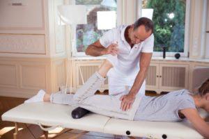 Roland Liebscher-Bracht unterstützt eine Frau bei einer Übung. Sie liegt bäuchlings und zieht ihr Bein in Richtung Gesäß, unter dem Knie befindet sich eine Faszienrolle.