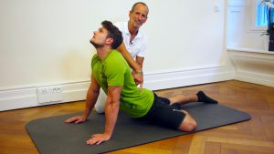 Ein Mann liegt bäuchlings auf einer Matte und stützt sich mit den Armen nach oben ab. Ein Bein ist seitlich angewinkelt. Roland Liebscher-Bracht zeigt auf seinen unteren Rücken.