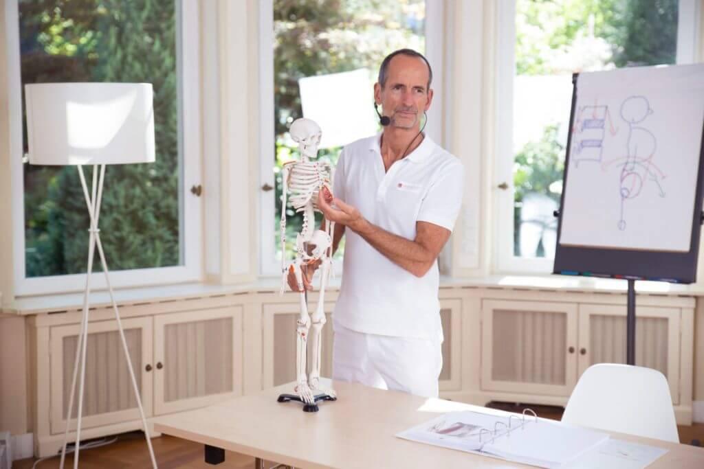 Roland Liebscher-Bracht erklärt etwas mithilfe eines Skelett-Modells.