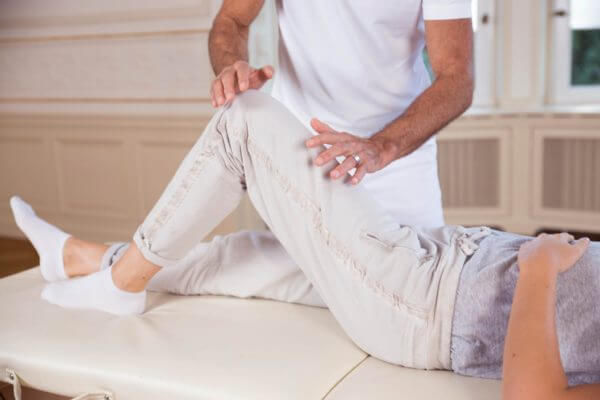 Roland Liebscher-Bracht deutet mit den Händen auf das angewinkelete Knie und Oberschenkel einer Frau, die rücklings auf einer Liege liegt.
