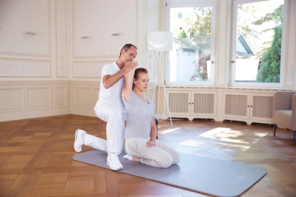 Roland Liebscher-Bracht zeigt einer Frau eine Übung. Dabei wird ihr Arm über den Kopf in Richtung Rücken gezogen.