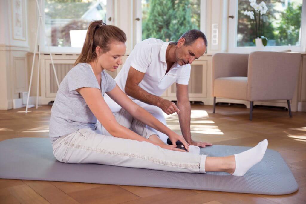 Frau rollt sich mit Faszienrolle im Sitzen über den Fuß. Das Bein ist angewinkelt, das andere ausgestreckt.
