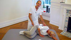 Ein Mann - Roland Liebscher - kniet über einer liegenden Frau in der Embryo-Stellung auf einer Iso-Matte und zeigt mit der Hand auf die Hüfte und mit der anderen an den Rücken