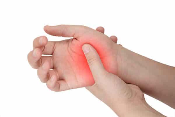 Handinnenfläche, andere Hand drückt auf das Daumengelenkt. Das Gelenk ist durch rotes Leuchten hervorgehoben.