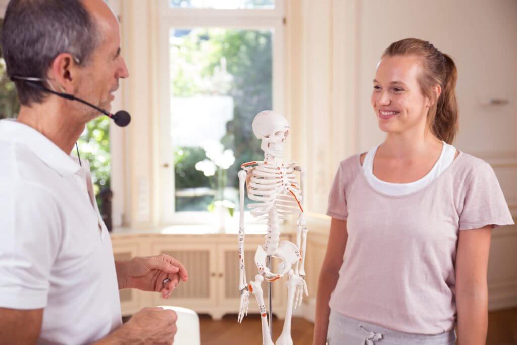 Roland Liebscher-Bracht und eine Frau im Gespräch. Zwischen ihnen steht auf einem Tisch ein Skelettmodell.
