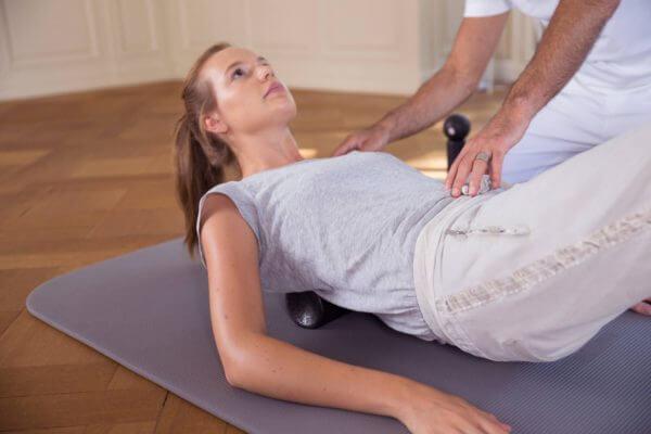 Eine Frau liegt auf einer Bodenmatte und rollt mit dem Rücken über eine Faszienrolle. Sie stützt sich mit den Armen leicht nach oben ab. Roland Liebscher-Bracht positioniert seine Hände auf ihrer Schulter und Bauchbereich.