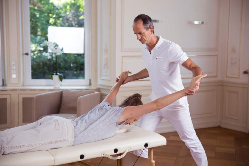 Roland Liebscher-Bracht zeigt einer Frau eine Übung. Sie liegt dabei bäuchlings auf einer Liege, er zieht an ihren Armen.